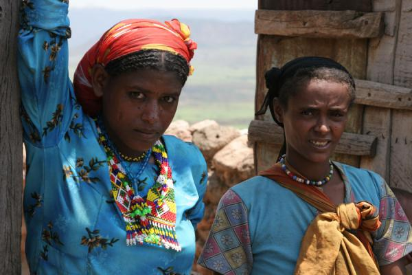 Two Koremi girls in brightly coloured dresses and jewellery | Koremi | Etiopia