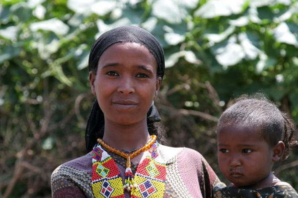 Boldly looking into the camera: Koremi woman with child | Koremi | Ethiopia