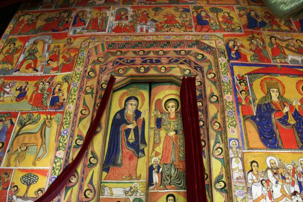 Wall and door full of biblical scenes in colourful murals in Ura Kidane Mihret | Lake Tana monasteries | Ethiopia
