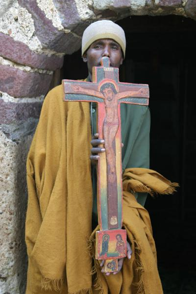 Priest showing old painted cross of Kibran Gebriel church | Lake Tana monasteries | Ethiopia