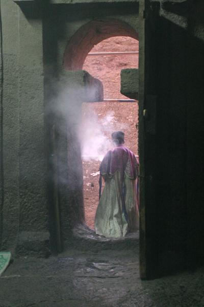 Priest walking out of Bet Medhane Alem before service | Lalibela Northern Cluster | Ethiopia