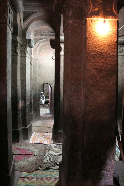 Interior of Bet Golgotha with priest | Lalibela Northern Cluster | Ethiopia