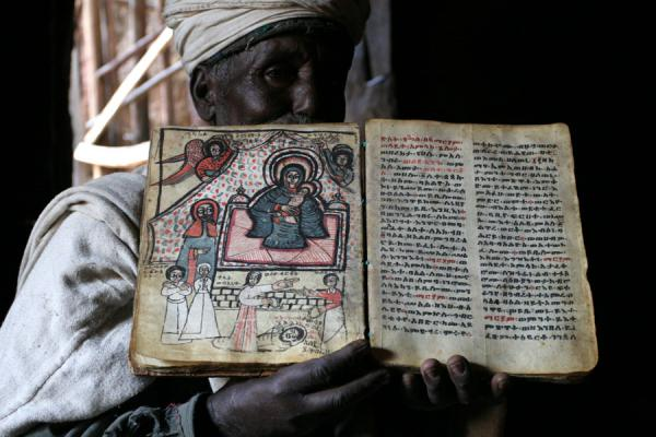 Priest of Bilbilla Chirkos showing a precious old goatskin book | Lalibela priests | Ethiopia
