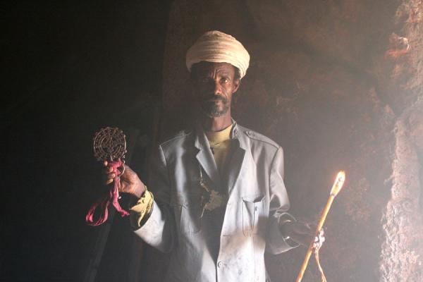 Priest with cross and candle in Bilbilla Chirkos | Lalibela priests | Ethiopia
