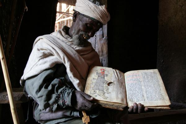 Priest in Bilbilla Giyorgis showing an old goat skin book | Lalibela priests | Ethiopia