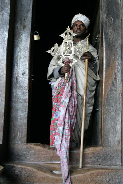 Priest of Yemrehanna Kristos showing cross in the doorway | Lalibela priests | Ethiopia
