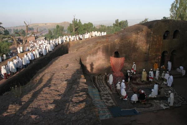 Worshippers near the trenches of the northwestern cluster complex; priests below | Lalibela Sunday Mass | Ethiopia