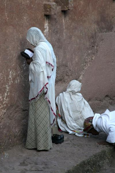 Woman praying against the wall of Bet Maryam, while other worshipper is about to kiss the floor | Lalibela Sunday Mass | Ethiopia