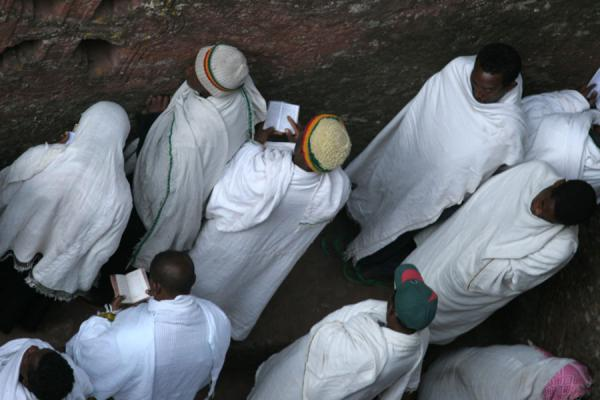 People standing in a trench next to Bet Mikael, praying on Sunday morning | Lalibela Sunday Mass | Ethiopia