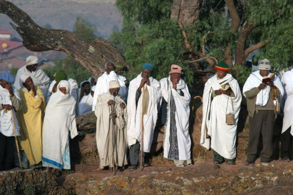 Men praying near the edge of the trench of Bet Mikael | Lalibela Sunday Mass | Ethiopia