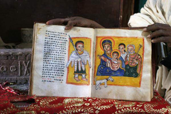 Priest showing one of the ancient goat skin books | Yeha | Ethiopia