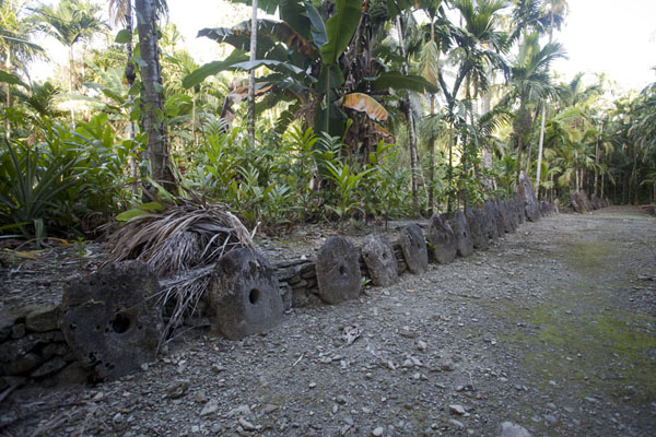 Picture of Okeu stone money bank (Federated States of Micronesia): Row of stone money disks from small to big and to small again at Okeu