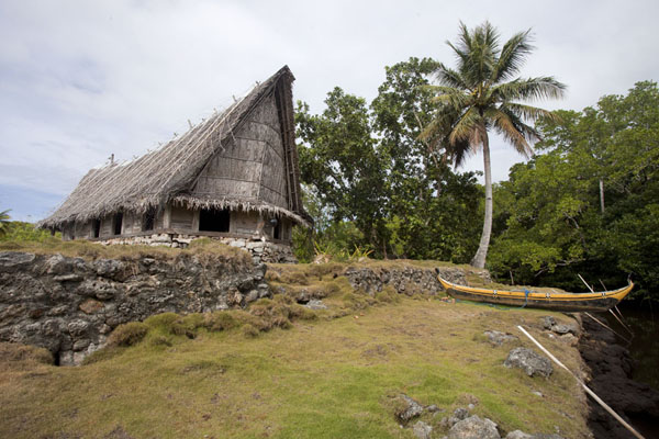 Looking up the men's house of Tamil with traditional canoe on the right | Tamil village |
