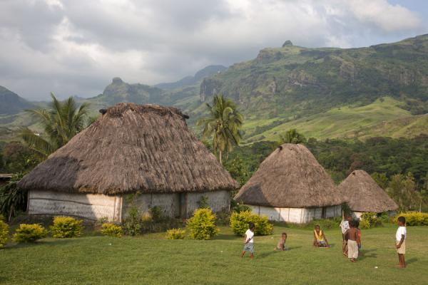 Row of traditional bure with mountains in the background | Navala | Fiji