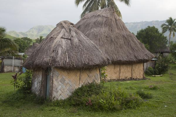 Bure lailai or small hut housing the toilet with bigger thatched roof house in the background | Navala | Fiji