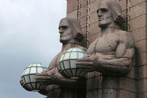 Picture of Taking care of light: serious statues carrying lanterns at Helsinki station