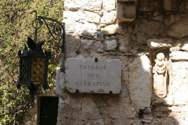 Streetscene in Eze: lantern, street sign and sculpture in the wall | Eze | France
