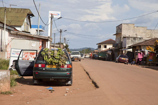 Foto de Car with bananas tied to the back waiting in the main street of BitamBitam - Gabón