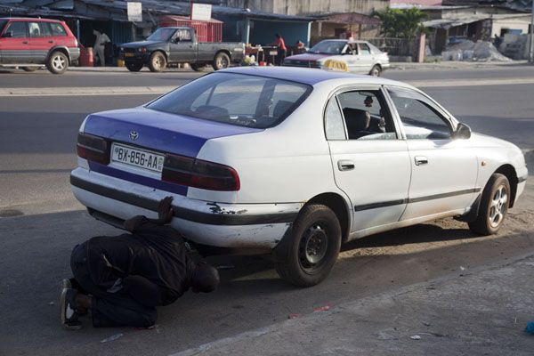 Picture of Driver fixing his taxiLibreville - Gabon