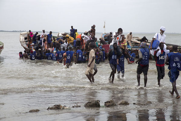 Picture of Strong guys carrying passengers to the pirogue for the trip across the river GambiaJufureh - Gambia