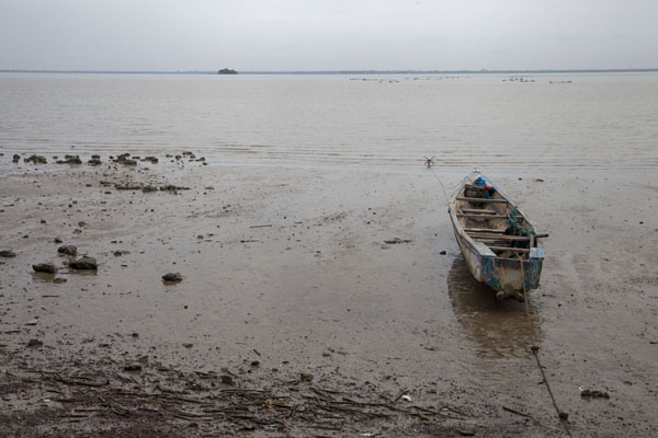 Stranded pirogue at low tide; James island in the distance - 甘比亚