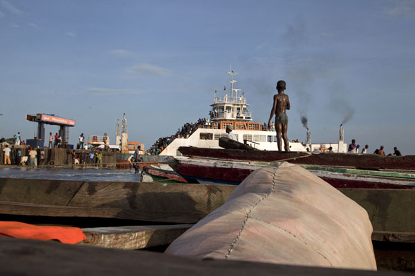 Boy standing on a bag on a pirogue watching the ferry dock | Jufureh Slave Museum | Gambia
