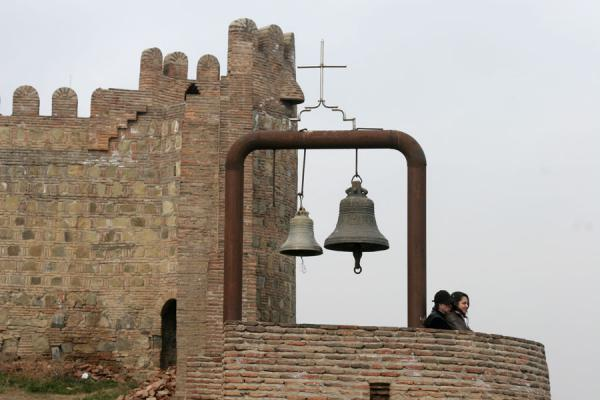 Foto di Detail of walls of Narikala fortress, with bell and kissing coupleTbilisi - Georgia
