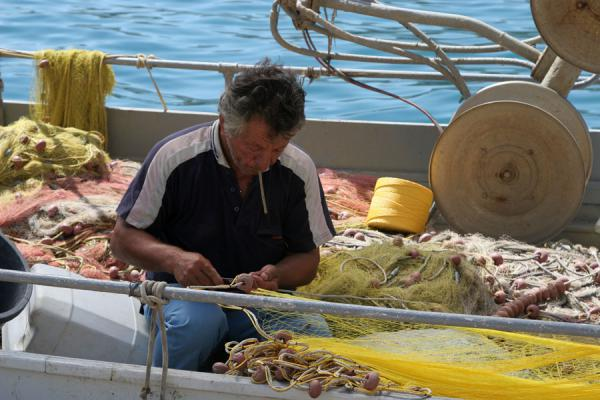 Picture of Poros (Greece): Fisherman repairing his nets on Poros