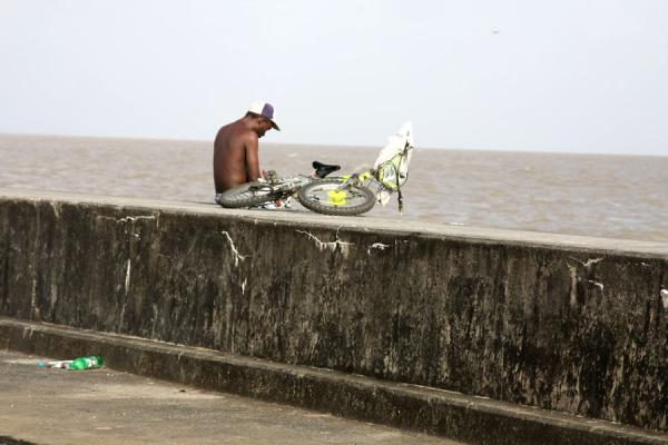 Having a break with a bicycle at the seawall | Georgetown seawall | 圭亚那