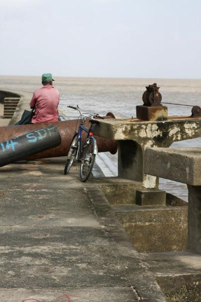 Picture of Georgetown seawall (Guyana): Man sitting on the seawall