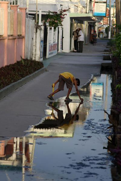 Foto van Boy picking something from the streetGeorgetown - Guyana