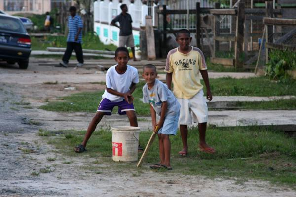 Boys playing cricket in the streets of Bartica | Guyanesi | Guyana