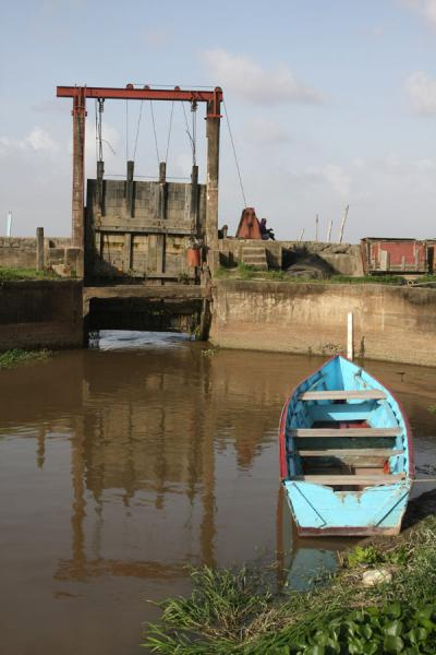Picture of West Demerara landscape (Guyana): Sluice or koker in the seawall, with boat