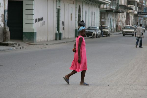 Woman in pink crossing a main street in Cap Haïtien | Cap Haïtien streetlife | Haiti