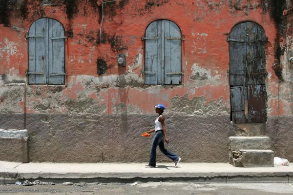 Picture of Haitian girl walking past a typical house in Cap HaïtienCap Haïtien - Haiti