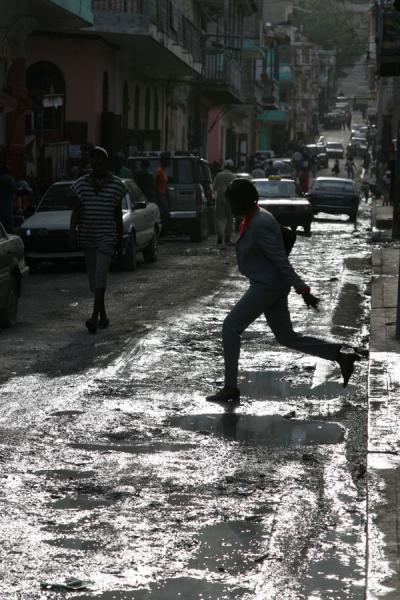 Foto di Woman stepping onto the street in Cap HaïtienCap Haïtien - Haiti