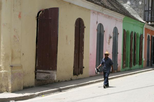 Picture of Man walking a street with colourful houses in Cap HaïtienCap Haïtien - Haiti