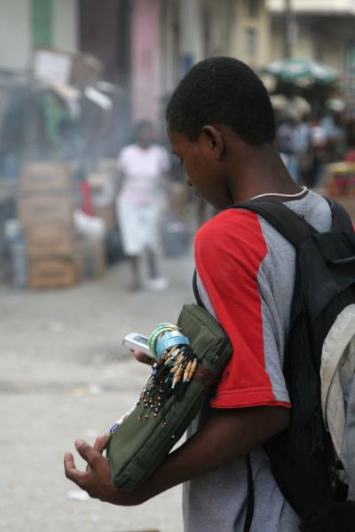 Street seller using his mobile phone in Cap Haïtien | Cap Haïtien street sellers | Haiti