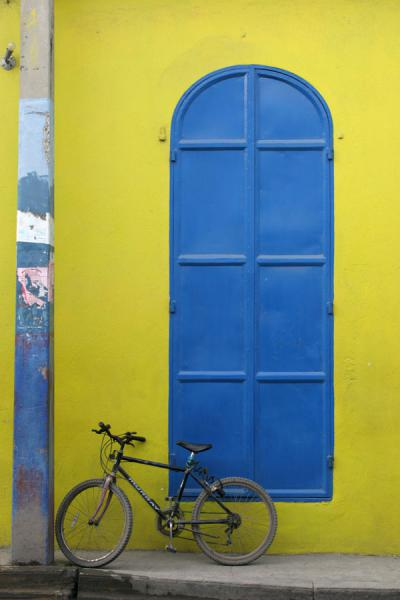 Bicycle parked against a yellow wall and blue door | Cap-Haïtien | Haiti