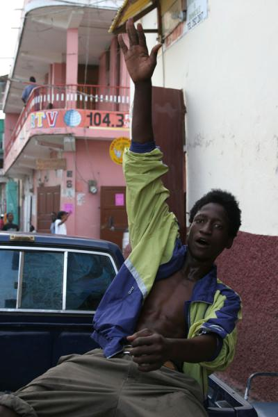 Picture of Haitian people (Haiti): Guy in Cap-Haïtien making himself seen in the back of a pick up truck