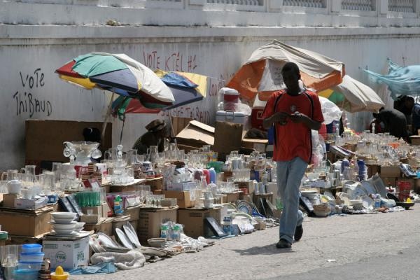 Haitian walking past exposed articles for sale in a street market | Port-au-Prince | Haiti