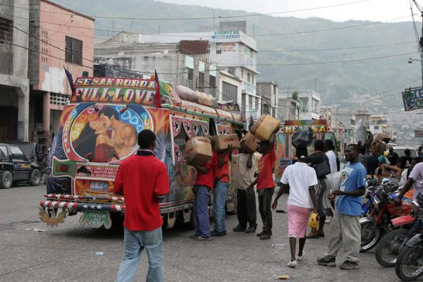 Picture of Port-au-Prince (Haiti): Colourful tap-tap with street sellers in Port-au-Prince