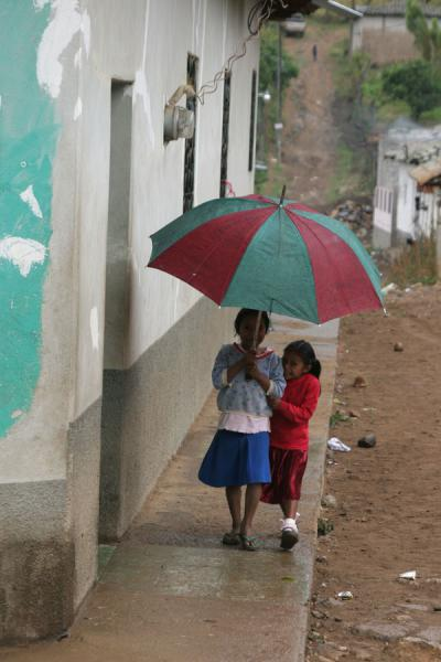 Two girls walking under umbrella on Belén Gualcho's square | Belén Gualcho | Honduras