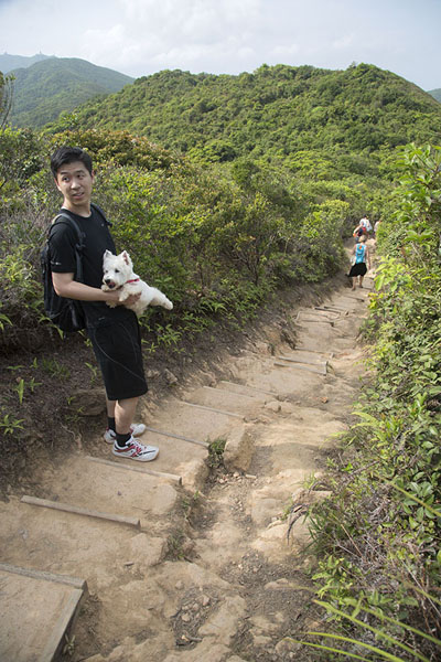 Picture of Man holding his dog on the Dragon's Back Trail - Hong Kong - Asia