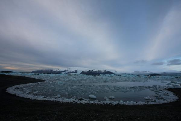 Picture of Icy Jökulsárlón under a cloudy sky with mountains and glacier in the backgroundJökulsárlón - Iceland
