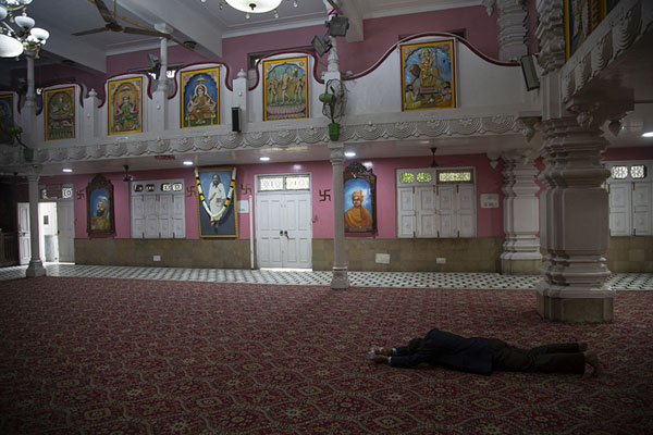 Man lying on the floor in prayer | Chhatarpur Mandir | India