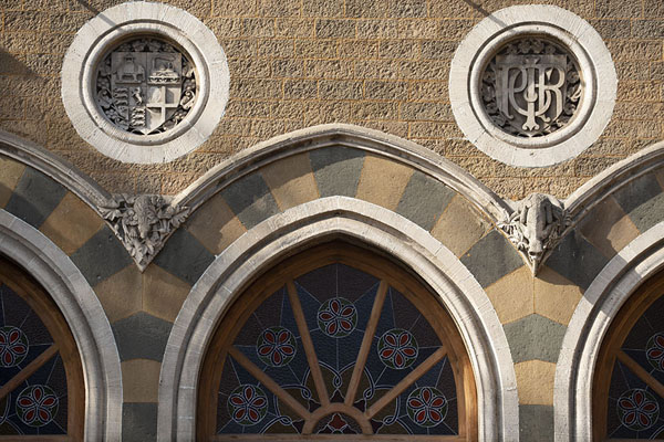 Close-up of the southern wall of the terminus building with ornaments over the windows and the emblem of the Indian railways | Chhatrapati Shivaji Terminus | Inde