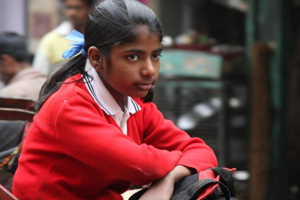 Picture of Indian girl in school uniform being transported on a cycle rickshaw