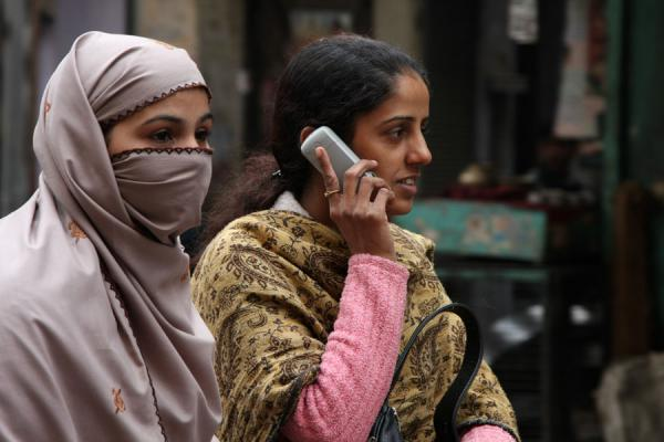 Picture of Making a call from the back of a bicycle rickshaw: young Indian women