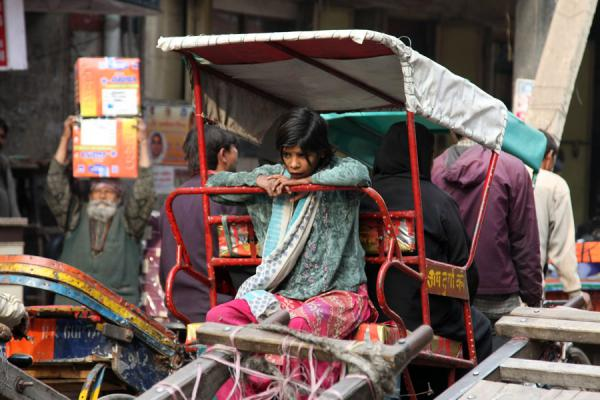 Girl on the back of a bicycle rickshaw, man carrying load | Cycle rickshaw riders | Inde